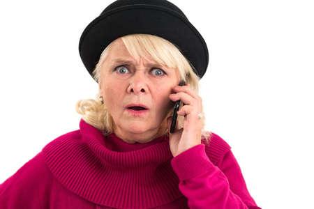 携帯電話で年配の女性が怖い。白い背景におびえた女性。脅迫の声を聞きます。 写真素材