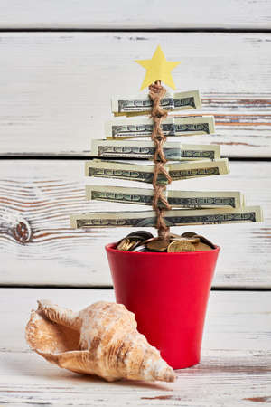christmas budget: Seashell and pot with coins. Christmas tree from dollars. Fund your dream vacation. Stock Photo