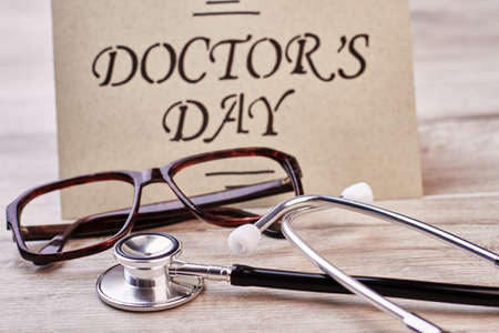 Stethoscope and brown frame glasses. Greeting card on Doctors Day.
