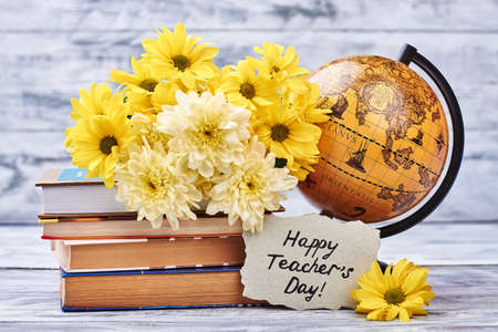 Yellow chrysanthemums, books and globe. Make your teacher happy today.