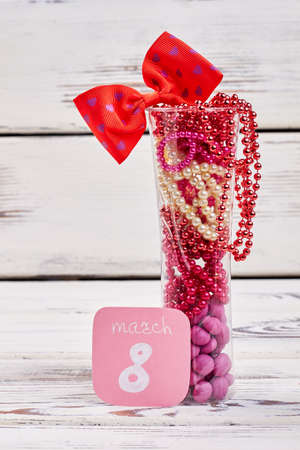 Glass with beads and dragee. 8th March greeting. Stock Photo