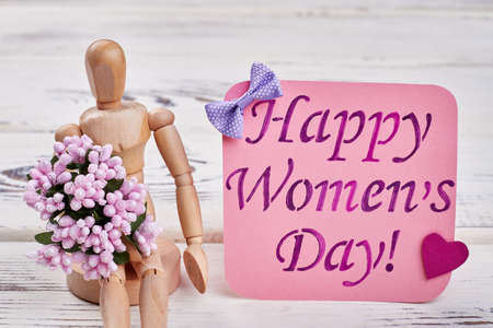 Wooden man, flowers and card. Womens day message.