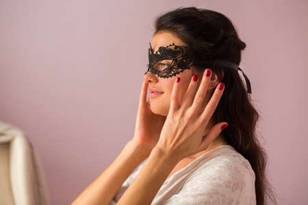 Woman wearing lace mask. Girl with dark hair. Recognize the beauty.
