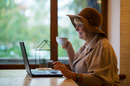 Smiling senior woman with laptop. Lady with cup near window. Coffee and fresh news. Stock Photo
