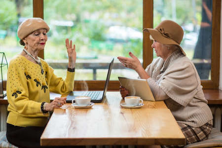 Women with gadgets in cafe. Coffee cups, laptop and tablet. Pros and cons of internet. Stock Photo