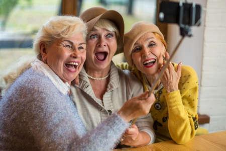 Women taking selfie at table. Three senior ladies laughing. Friendship is priceless. Stock Photo