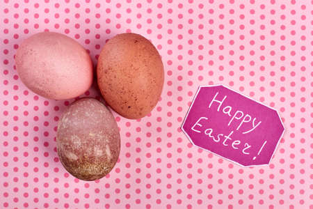 Eggs on pink background. Happy Easter card. Easter comgratualtory composition. Stock Photo