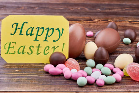 Happy Easter card, colorful sweets. Candies on wooden surface. Stock Photo