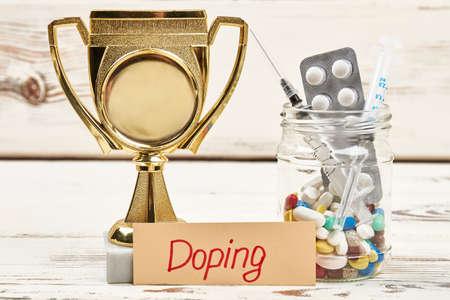 Syringe, pills and award. Stimulation of physical activity.