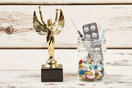 Pills in glass and award. Drugs banned in sport.