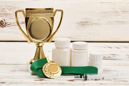 カップ、メダル、丸薬。スポーツの薬剤の使用。