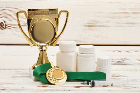 Cup, medal and pills. Drug use in sports.