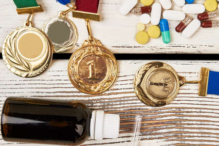 Medals, pills and bottle. Issue of doping in sport. Stock Photo