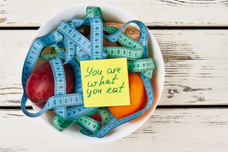 what to eat: Note and bowl with fruits. You are what you eat. Stock Photo