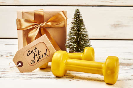 Fir-tree, dumbbells, box and card. New year resolutions.