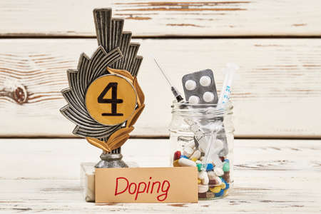 Drugs, award and syringe. Physical activiy with doping. Stock Photo