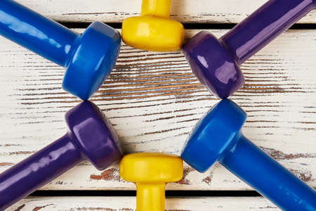 get a workout: Coloured dumbbells on wooden backdrop. Key to healthy life. Stock Photo