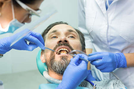 concave: Dental doctors working with patient. Dentist using concave mirror. Stock Photo