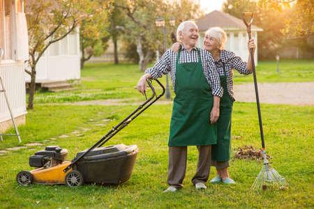 Glimlachend paar oude tuinlieden. Gelukkige man met grasmaaier. Koop een tuin. Stockfoto