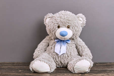 Gray teddy bear. Soft toy on wooden surface.