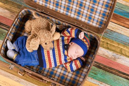 Little child sleeping in suitcase. Small kid and toy dog. Tips for travelling with baby.