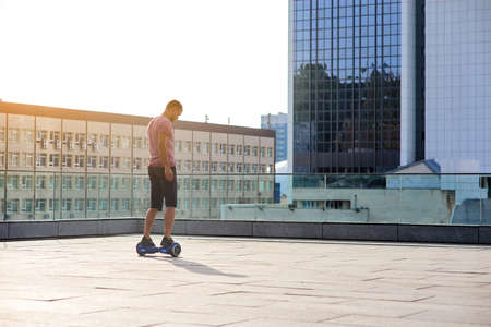 Man riding hoverboard. Guy on city background. Stock Photo