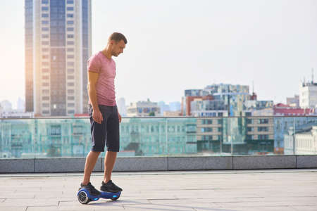 invent: Man riding hoverboard, city background. Guy outdoors at daytime.
