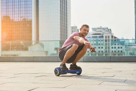 Young male riding hoverboard. Man in the city, daytime.