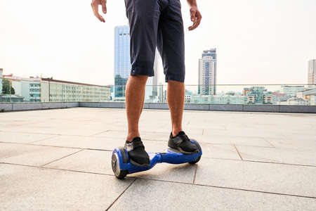 Legs on hoverboard, city background. Person riding blue gyroscooter. Stock Photo