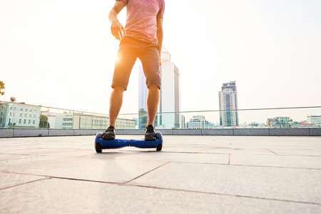 Man riding hoverboard, city. Guy on blue gyroboard.