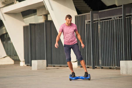 Man riding hoverboard. Young male in the street.