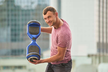 Man holding gyroboard. Person with a gadget outdoors. Hoverboard with improved battery capacity. Stock Photo