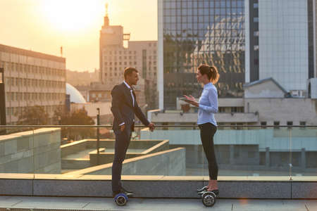 Mensen uit het bedrijfsleven op de achtergrond van de stad. Man en vrouw op hoverboards. Hoe succesvol te worden.