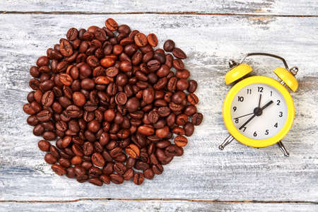 Alarm clock and coffee beans. Coffee grain on wooden background. Time to have a lunch. Imagens