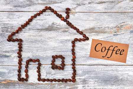 pause icon: Coffee beans and message. House from coffee, wooden table.