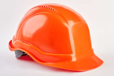Plastic safety helmet isolated. Orange protective hat, white background. Industrial protection.