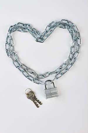 enclose: Chain in shape of heart. Lock, key, chain, white background. Concept of love safety.