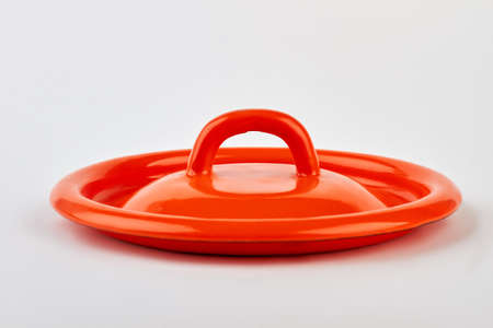Front view of red lid. Single kitchenware object, white background. Фото со стока