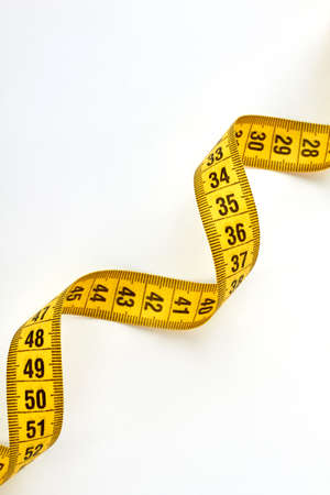 millimeter: Twisted yellow measuring tape. Measure tool isolated on white. Stock Photo