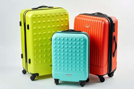 Kleurrijke koffers om te reizen. Drie kleurrijke koffers, witte achtergrond. Zomervakantie concept.