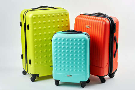 Colorful suitcases for travelling. Three colorful suitcases, white background. Summer vacation concept. Foto de archivo