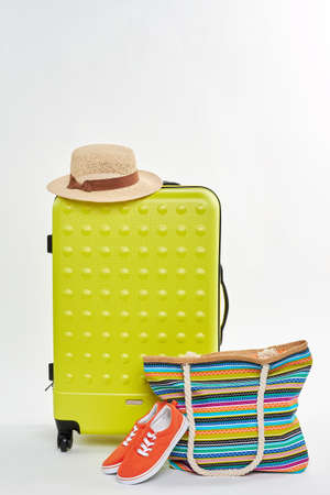 Wheeled suitcase and sea accessories. Hat, shoes, handbag, suitcase, white background.