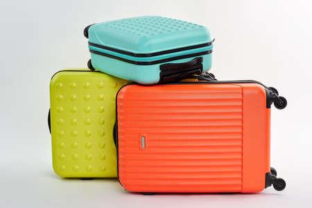 Koffers op wiel, witte achtergrond. Kleurrijke voorwerpen voor reisreis.