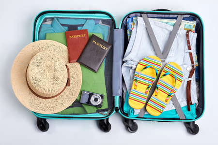 Beach accessories in opened suitcase. Travelling wheeled bag, different clothes. Imagens