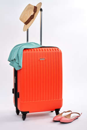 Red suitcases and woman accessories. Sandals near wheeled luggage, white background. Stock Photo