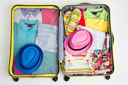 Woven hats and clothing in suitcase. Yellow wheeled bag full of clothes.