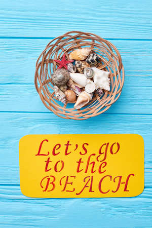 oceanic: Seashells in decorative wooden basket. Paper with message, colored background, top view. Oceanic souvenirs from beach vacation. Stock Photo