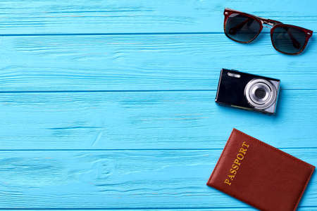 Glasses, camera, passport, wooden background. Concept of travel, blue background.