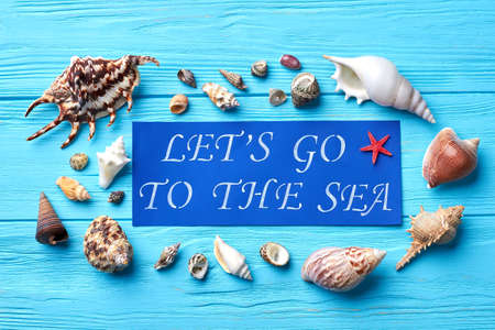 Composition from sea shells, paper note. Sea shells around blue paper message. Summer vacation concept.