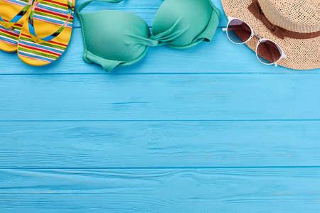 Woman beach accessories on sea background. Slippers, swim bra, glasses, hat. Concept of sea vacation.